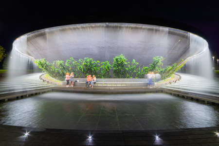 Waterfall flows in streams into granite bed of artificial river. Fountain 'Infinity' in form of huge bowl. Stock Photo