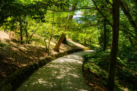 Curved footpath surrounded by flowers, green plants and grass in a beautiful park. Stock fotó