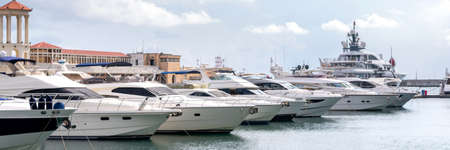 Yachts and speed boats at harbor. Power boats moored in marina. Sea coast pier. High class lifestyle. Yachting. Expensive toys. Sea transport. Journey. Expensive boats at the pier. Foto de archivo