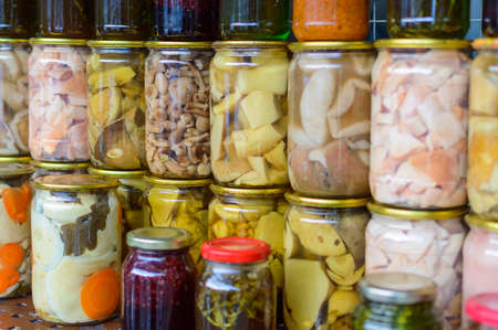 pickled mushrooms in a glass jar on street market