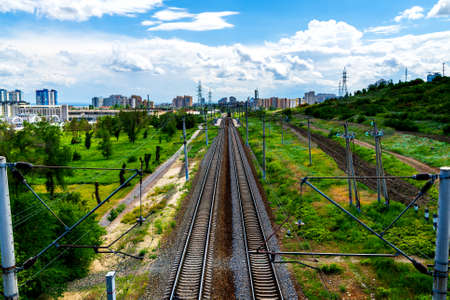 Straight railroad track in industrial area of city.