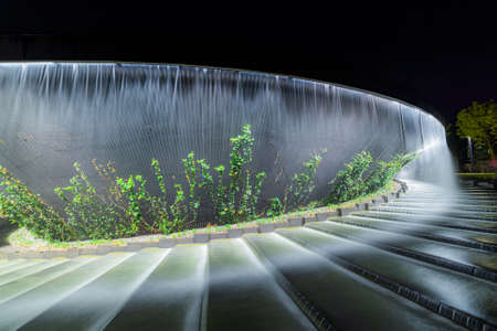 Waterfall flows in streams into granite bed of artificial river. Fountain 'Infinity' in form of huge bowl.