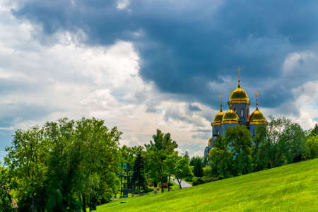 Orthodox church with golden domes on slope of hill.
