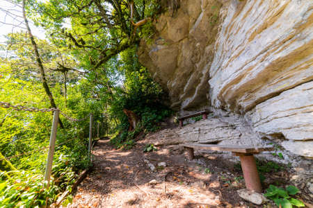 Textures of various stone layers on cliff. Benches in rest place on hiking trail.