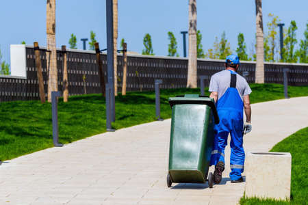 Janitor rolls trash can on wheels. Cleaning service in modern park. Zdjęcie Seryjne