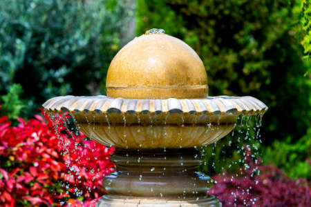 The top part of the fountain. Bowl and sphere in the light of morning sun.