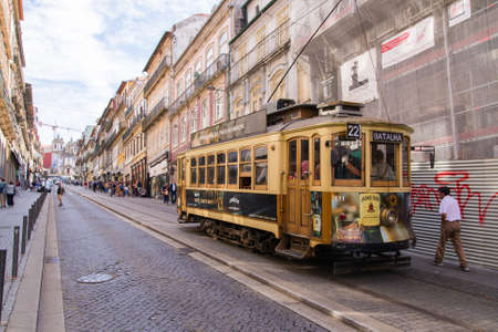 Porto, Portugal - October 06, 2018: Vintage wooden tram in city center Porto. Traditional trams rattle through the narrow streets transporting locals and tourists. Heritage tramcar. Travel concept.