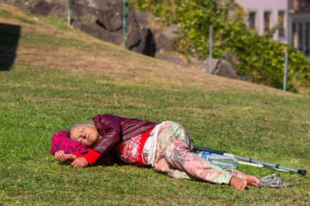 Portugal, Porto, October 06, 2018: Elderly woman with crutches lies and sleep on green grass in park. 新闻类图片