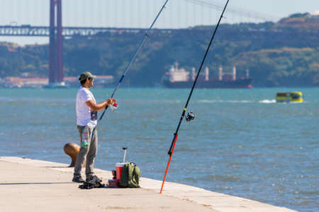 Portugal, Lisbon, October 08, 2018: A man with a fishing rod is fishing on embankment. 新闻类图片