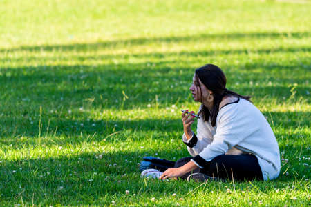 Portugal, Lisbon, October 09, 2018: Young woman use smartphone seating on grass in a park. 新闻类图片