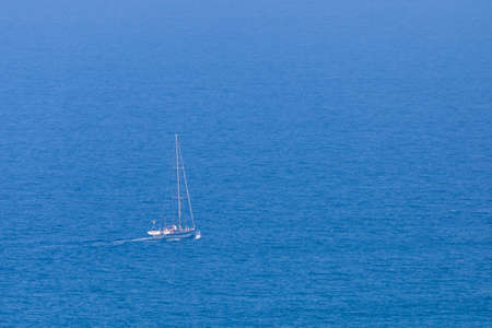 White sail boat on blue water of sea. Minimal composition with copyspace.
