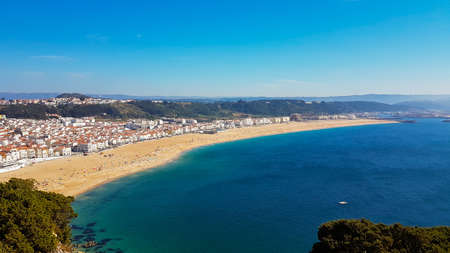 Bird's-eye view on Nazare beach riviera on the coast of Atlantic ocean with Nazare town. Portugal.