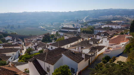 Obidos, Portugal: Cityscape of the town with medieval houses, wall and the Albarra tower. Obidos is a medieval town still inside castle walls, and very popular among tourists. 免版税图像