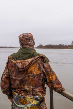 Man in camouflage trousers and jacket with hood catches fish on river in a cloudy day. Zdjęcie Seryjne