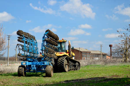 Agricultural tractor with equipment for working in field.