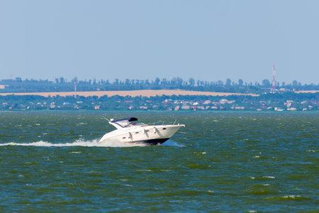 Power speedboat cruising in the sea bay.