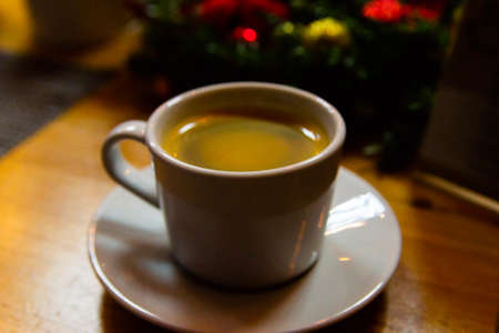 Coffee in brown cup on wooden table.