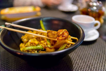 Thai food-Stir fried Noodle, Pad Thai in dark plate with sticks. Zdjęcie Seryjne