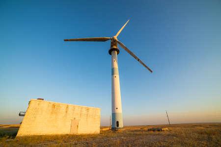 Old abandoned wind turbines in the desert landscape.