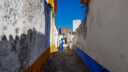 a narrow street inside of the obidos castle in Portugal.