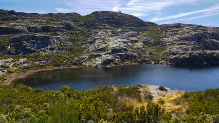Panoramic view from the peak of the Serra da Estrela mountains and natural park in the Guarda district, Beiras Region, Portugal. Mainland Portugal's highest mountains - 1993m. Reservoir in foreground