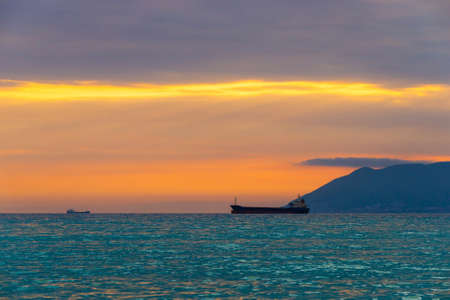 Cargo ship sailing away at the colorful sunset.
