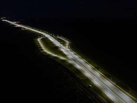 Night roads panoramic background, bird eye view on illuminated highway, modern motorway.