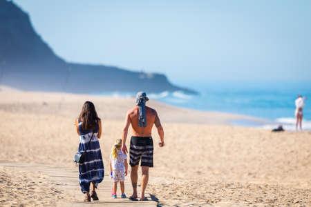 Portugal, Praia Santa Rita Norte, October 04, 2018: Family with one child walking on sand beach. 新聞圖片