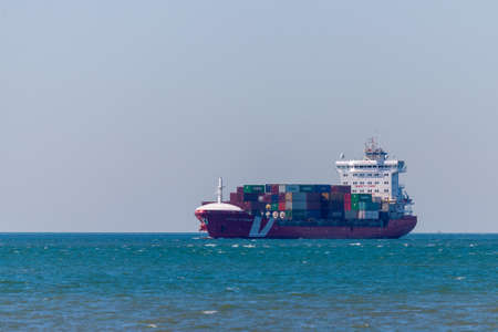 Portugal, Lisbon, October 08, 2018: Container ship sailing in to the seaport.