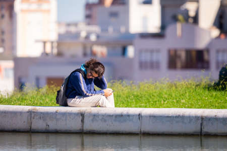 Portugal, Lisbon, October 09, 2018: Young man waiting SMS sitting on fountain border