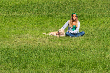 Portugal, Lisbon, October 09, 2018: Young beautiful portuguese woman with dog on a green grass in sunny day.