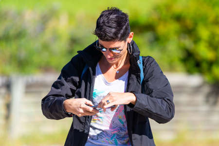 Portugal, Lisbon, October 09, 2018: Modern woman with short black hair use smartphone.
