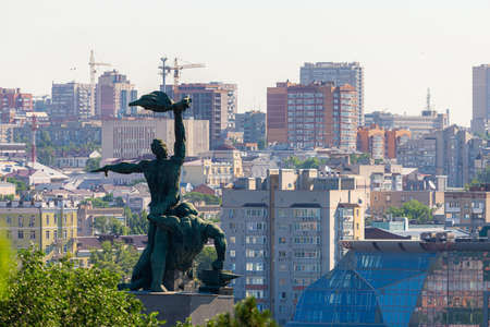 Russia, Rostov on Don, June 27, 2020: The monument of the strike of 1902, two men on a concrete pedestal in Rostov-on-Don on a hill. City background.