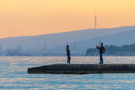 Russia, Kabardinka, May 02, 2019: Couple make a photo at yhe concrete sea pier. 新聞圖片