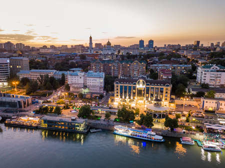 Rostov-on-Don, Russia - July 06, 2020: aerial view of the Don River and embankment at sunset. Bridges, buildings, light of lanterns is reflected in water. Beautiful sky. City on a summer evening from above. 新聞圖片