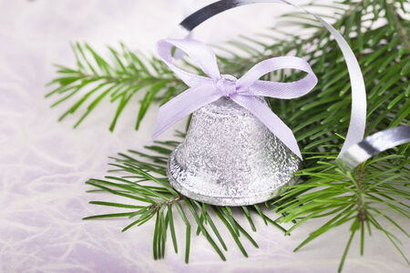 Christmas bell with fir-tree twigs on abstract background photo
