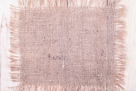 lacerate: Brown burlap patch  on wooden background with lacerate edge