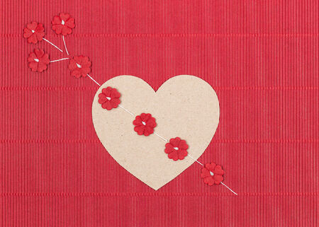 Cardboard heart with paper flower arrow on red background photo