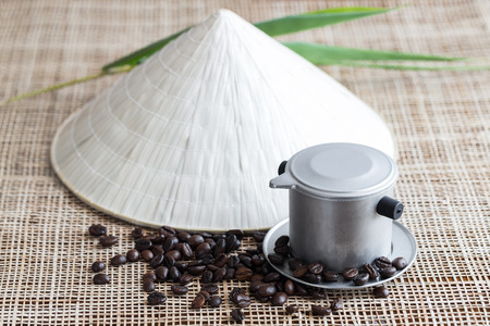 Vietnamese coffee brewing pot with coffee beans and conical hat Stock Photo