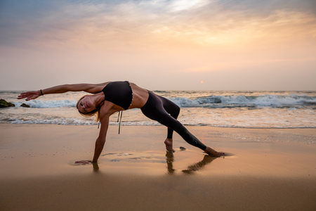 Middle age woman in black doing yoga on sand beach in India at sunset. Healthy lifestyle. Reklamní fotografie