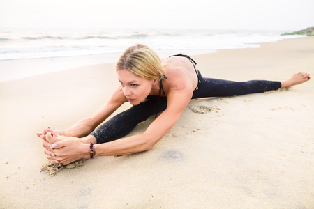 Slim strong middle age woman in black practicing yoga doing the splits on sand beach close-up with copy space. Yoga in India. Healhy lifestyle concept. Reklamní fotografie