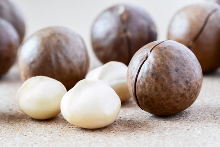 Whole Macadamia nuts and kernel on brown background, close-up. Healthy food.