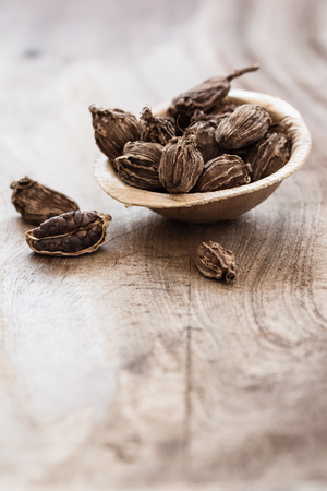 Black cardamom in a bowl on wooden background indian spice close-up