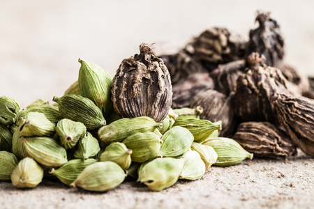 Black and green cardamom whole seeds on wooden background. Indian spice. Close-up.