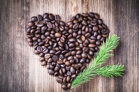 Coffee beans in the shape of heart with fir tree branch on wooden background, top view. Space for text 스톡 콘텐츠