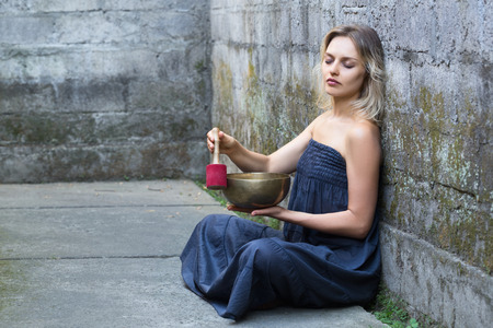 Beautiful young woman with closed eyes is sitting and using a singing bowl. Medetation yoga concept. Grey blue colors.