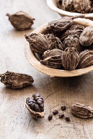 Black cardamom whole seed in a bowl on wooden background indian spice close-up