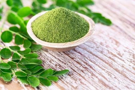 Moringa powder (Moringa Oleifera) in coconut bowl with original fresh Moringa leaves on wooden background. Healthy product, superfood, vitamin. Stock Photo