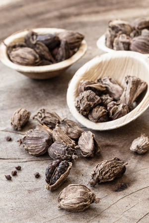 Black cardamom whole seed in a bowl on wooden background indian spice close-up selective focus