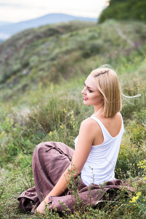 Beautiful smiling blonde young woman sitting on green grass in white top and brown skirt hill view outdoors